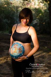 Fotografía de una mujer embarazada con un bellypainting (barriga pintada por Colorehadas) de los looney tunes. Ella está de pie mirando a cámara acariciándose la barriga. El pelo le tapa el ojo derecho, pero el ojo izquierdo mira directamente a cámara