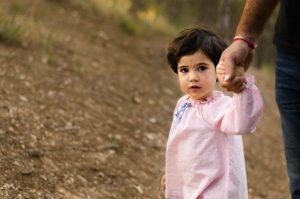 Una niña y su papá están paseando por el monte cogidos de la mano. En la fotografía solo se ve a la niña agarrada fuerte a su padre y mirando interesada a cámara sin sonreir