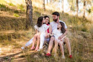 Familia de cuatro sentada en el monte, con las manos entrelazadas y mirándose entre sí