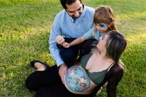 Fotografía de una familia sentada sobre césped. Todos se miran entre sí. La mamá tiene la barriga pintada con dos sirenas, que simulan a la bebé que está dentro de la barriga y a la hermana mayor.