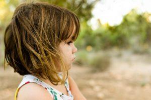 Fotografía a color hecha en Cotocuadros. Aparece una niña de perfil donde se resalta el pelo suelto cortado por el hombro y moviéndose por el viento.