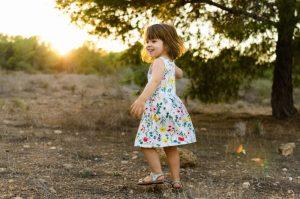 Fotografía a color hecha en Cotocuadros. Aparece una niña dando vueltas divertida en plena puesta de sol.