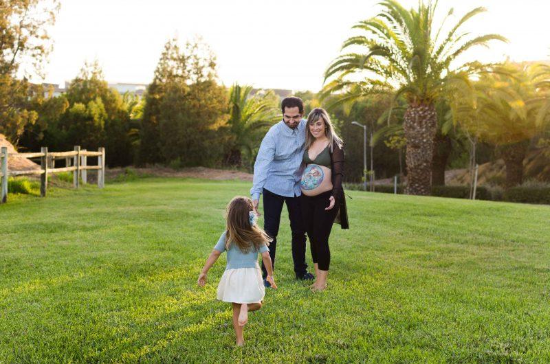 Fotografía a color de una familia en el campus de Espinardo. Papá y mamá están de pie, cogidos por la cintura y mirando a su hija que está corriendo hacia ellos descalza. La mamá está embarazada y tiene un dibujo en su barriga pintado por Colorehadas
