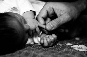 Fotografía en blanco y negro de las manos de un bebé y la mano de su papá. Los dedos índice y pulgar de la mano del papá cogen ligeramente el dedo meñique del dedo del bebé. Se aprecia la gran diferencia de tamaño que hay entre los dos.