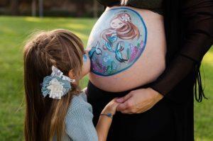 Niña de 4 años besando la barriga embarazada y pintada de su mamá. La mamá y la niña tienen las manos cogidas junto a la barriga. La barriga tiene dos sirenas pintadas representando a la bebé de dentro de la barriga y su hermana. Fotografía realizada en el Campus de Espinardo