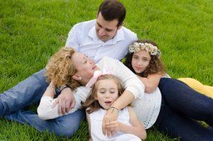Fotografía de una familia formada por cuatro personas: papá, mamá y dos niñas. El papá está sentado y la mamá está tumbada encima de él. Una de las niñas está semitumbada detrás de mamá y junto a papá. Y la otra niña está tumbada delante de mamá sobre la barriga de ésta jugando con un diente de león. Papá y mamá se miran y sonríen entre ellos. Y la niña que está detrás mira tranquila a cámara. Fotografía hecha en Cieza