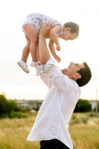 Fotografía de un papá lanzando al aire a su hija. Ambos se miran y se sonríen. El papá solo está fotografiado de caderas hacia arriba. Es una foto en vertical y a contraluz