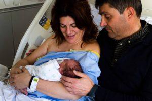 Fotografía a color de una familia compuesta por mamá, papá y su bebé recién nacido. Están en el hospital Virgen de la Arrixaca de Murcia, ambos sentados sobre la cama del hospital. El bebé está tumbado en brazos de mamá. Los papás miran al bebé y sonríen.