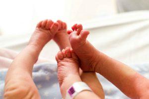 Fotografía a color de las piernas y pies de dos bebés mellizos recién nacidos. Se nota que tienen las piernas y los pies en movimiento, aunque los pies de uno de los bebés están sobre la pierna de otro de los bebés. A uno de ellos se le ve la tobillera del hospital. Fotografía tomada en el Hospital Quirón de Murcia