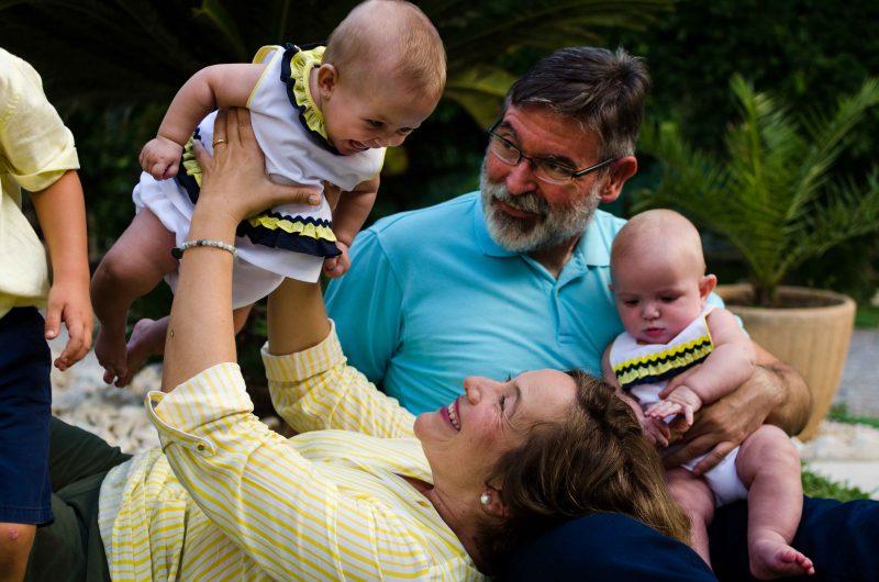 Fotografía de una familia compuesta por papá, mamá y tres hijos. Mamá está tumbada con la cabeza apoyada sobre la pierna de papá, quien está sentado con uno de los bebés encima de su otra pierna. Ese bebé está mirando hacia el pelo de su mamá y, por la posición de las manos, se nota que quiere cogerle el pelo. Mamá está sonriendo, mirando y elevando al aire a su otro bebé, quien a su vez le sonríe. Papá también está mirando al bebé que está en el aire. Y del tercer hijo solo aparece a la izquierda de la imagen un brazo y medio cuerpo.
