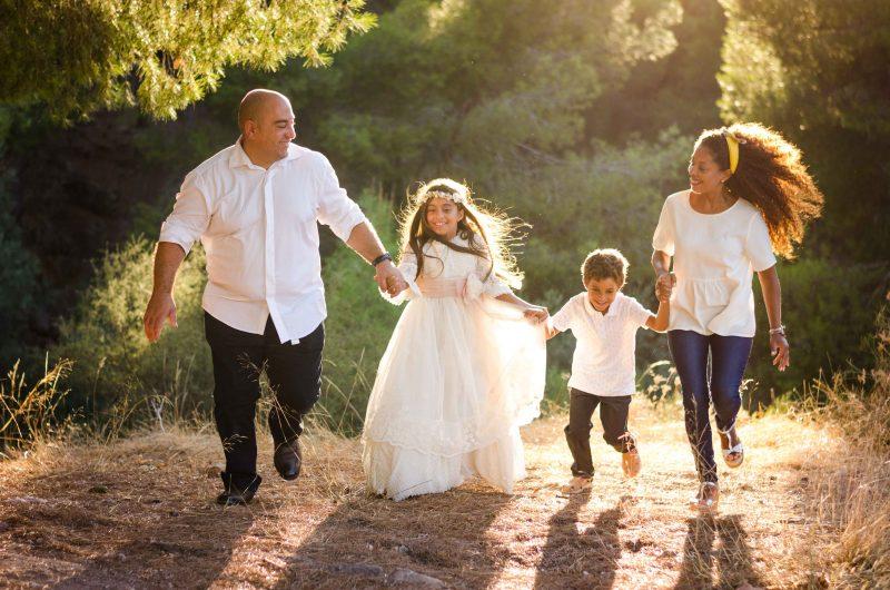Imagen de una familia corriendo al atardecer en la Fuensanta de Murcia. Están los cuatro cogidos de las manos. A la izquierda de la imagen papá, luego la niña vestida de primera comunión, luego el niño y por fin la mamá. Todos se miran entre ellos, están cogidos de las manos y se ríen.
