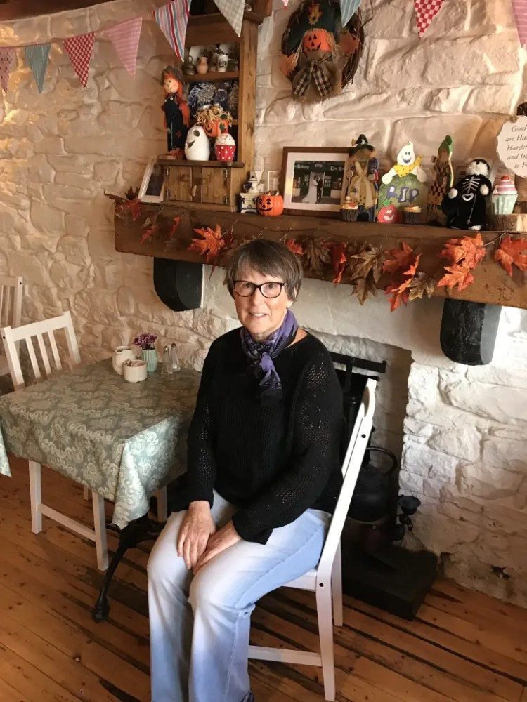 Image of the author, Martha Geaney, sitting inside at Curry's Cottage