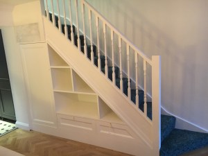 Under stair cupboard with open shelving and cupboards