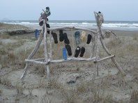 Driftwood sculpture on Bryans Beach, Ohiwa. The footwear are called jandals in NZ