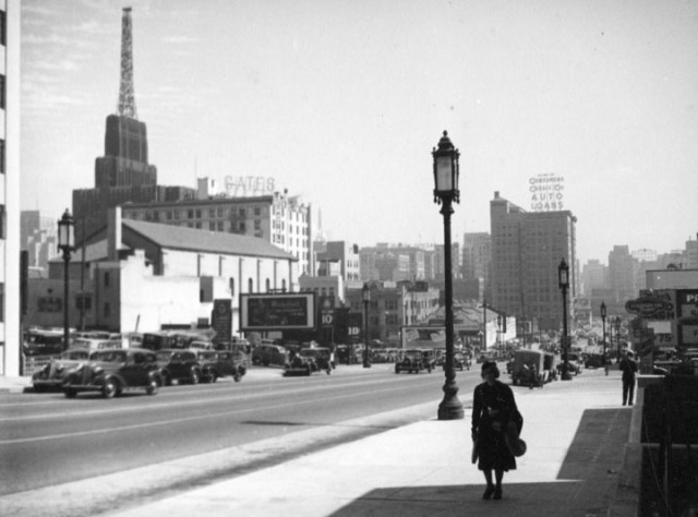 Woman walking down Wilshire Blvd with the tower of the Richfield Building looming in the background