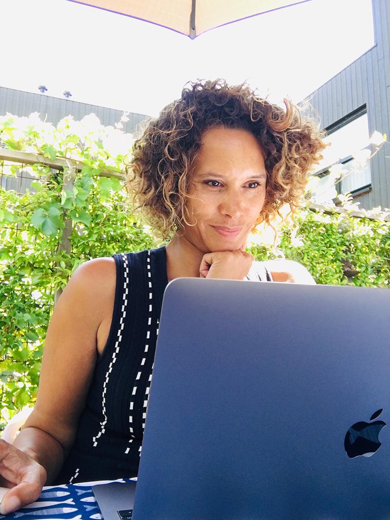 Maruga werkt in de tuin achter haar laptop