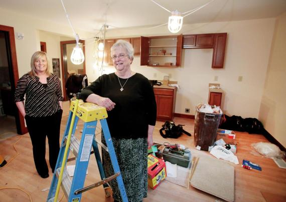 Sister Stella Olson (right) and YWCA Executive Director Erin Prochnow pose for a photo in October 2015 when a room was being remodeled to be used as a transitional shelter for women. Forum file photo