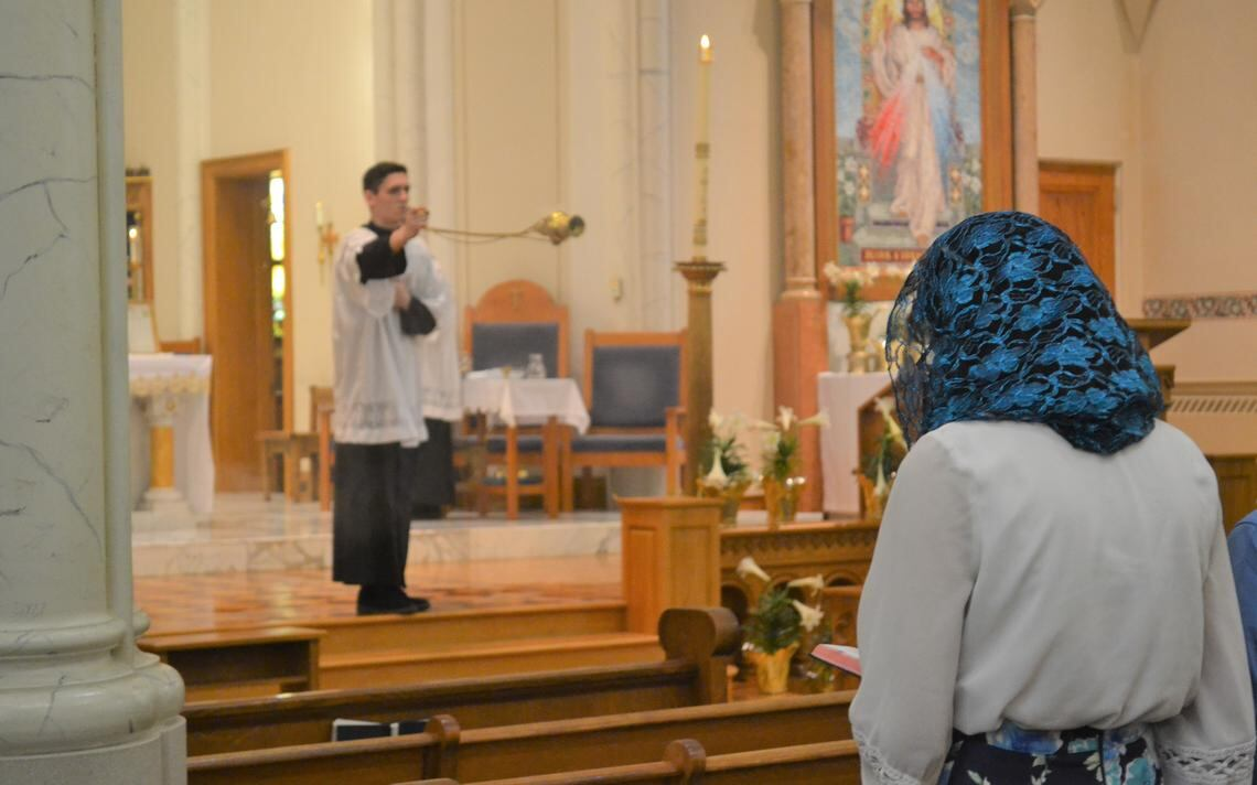 Smoke from incense rises as Ethan Devitt swings the thurible toward the congregation Sunday, April 18, 2021, during a Mass at St. Mary's Cathedral in downtown Fargo. Roxane B. Salonen / The Forum