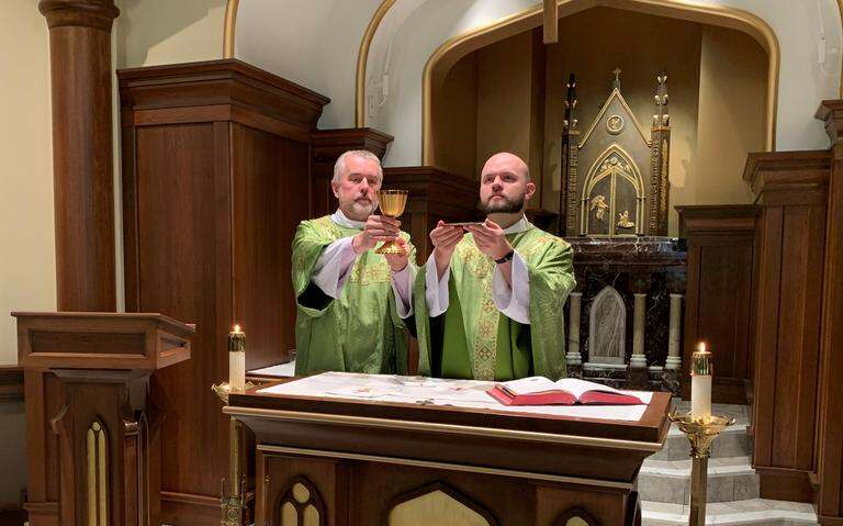 Deacon Ben Seitz (left) and Fr. Eric Seitz pose for a photo recently in the St. Anne and Joachim Catholic Church daily Mass chapel in Fargo. Here, they represent the sacrificial offering of Jesus' body and blood, which takes place at the crux of every Catholic Mass, every day, throughout the world. Special to The Forum