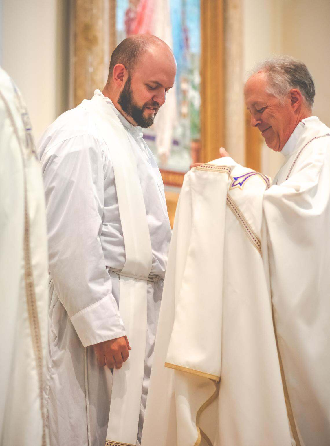 Fr. Paul Duchschere (right) of Sts. Anne and Joachim Catholic Church in Fargo, the former home parish of Fr. Eric Seitz, prepares to place the priest chasuble (robe) on the new priest, Fr. Eric Seitz, at his ordination Mass on Aug. 8, 2020, at St. Mary's Cathedral in Fargo. Photo by Kristina Lahr / New Earth / Special to The Forum