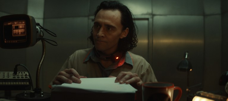 """Tom Hiddleston as Loki is told to sign a document of all the things he has ever said in Loki's episode one titled """"Glorious Purpose"""" on Disney Plus."""