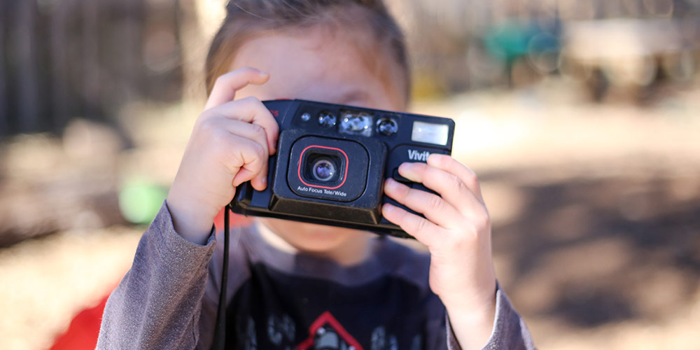 child taking photograph with toy camera