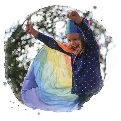 girl pretending to fly in rainbow cape
