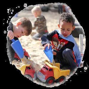 two preschool boys play in sandbox together