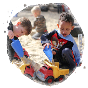 two preschool boys play in sandbox together