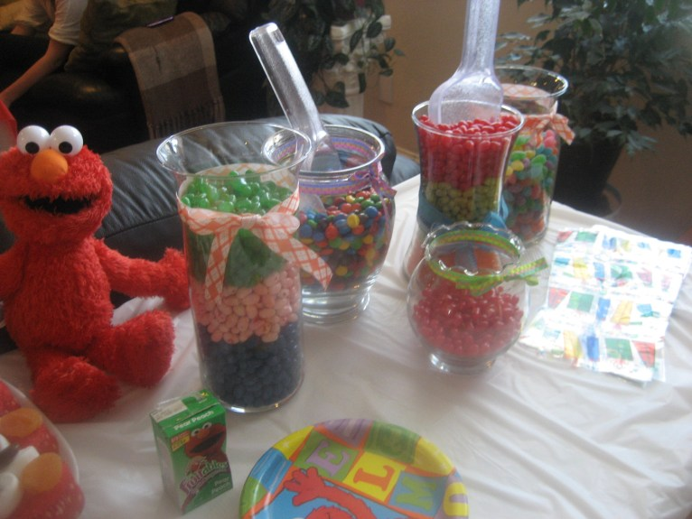Candy displayed in candy jars with scoopers.