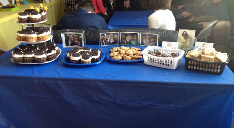 Blue table cloth over a table. Cupcakes, cookies and donuts on top.