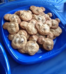 Chocolate chip cookies shaped like Mickey Mouse head on a blue square plate.