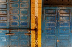An old door next to a large windowfront, both locked. The bichrome complementing colours are striking.