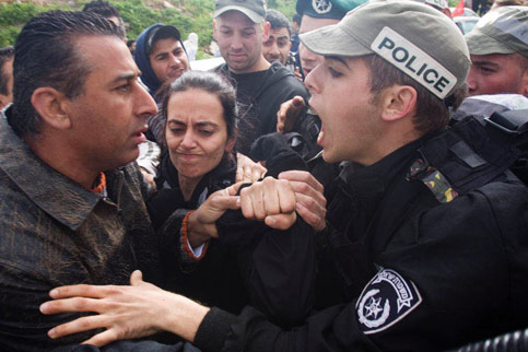 Israeli riot police argue with Palestinian and Jewish citizens of Israel protesting against racism outside a polling station in Um al-Fahem during the Israeli elections, 10 February 2009. (Oren Ziv/ActiveStills)