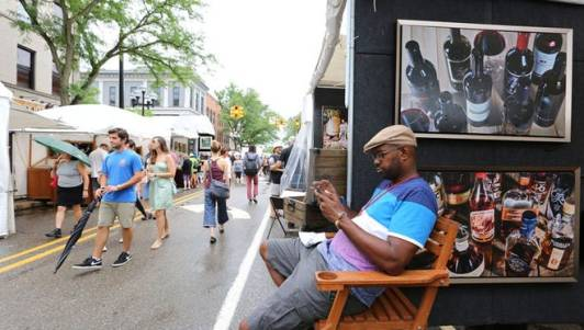 Marcus Ryan of Atlanta, Ga. is a mixed media artist who is passing the time on his phone during the Ann Arbor Art Fair on its final day Sunday, July 24, 2016.