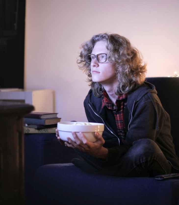 focused man with bowl of popcorn watching tv at home