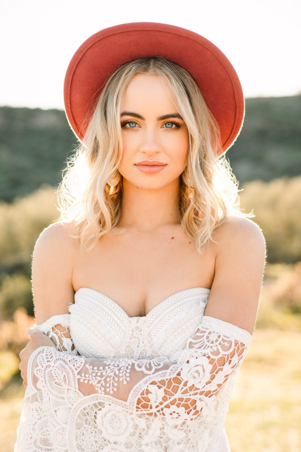 Bride in bold hat by Mary Costa Photography