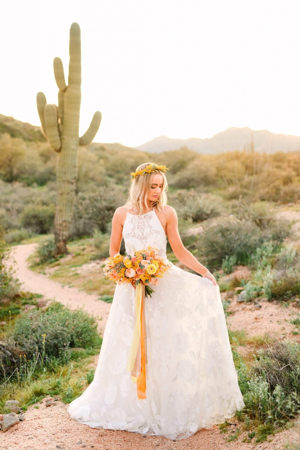 Bride in cactus desert with yellow bouquet by Mary Costa Photography