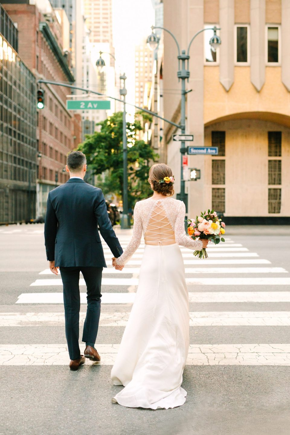 Bride and groom walking on NYC street by Mary Costa Photography
