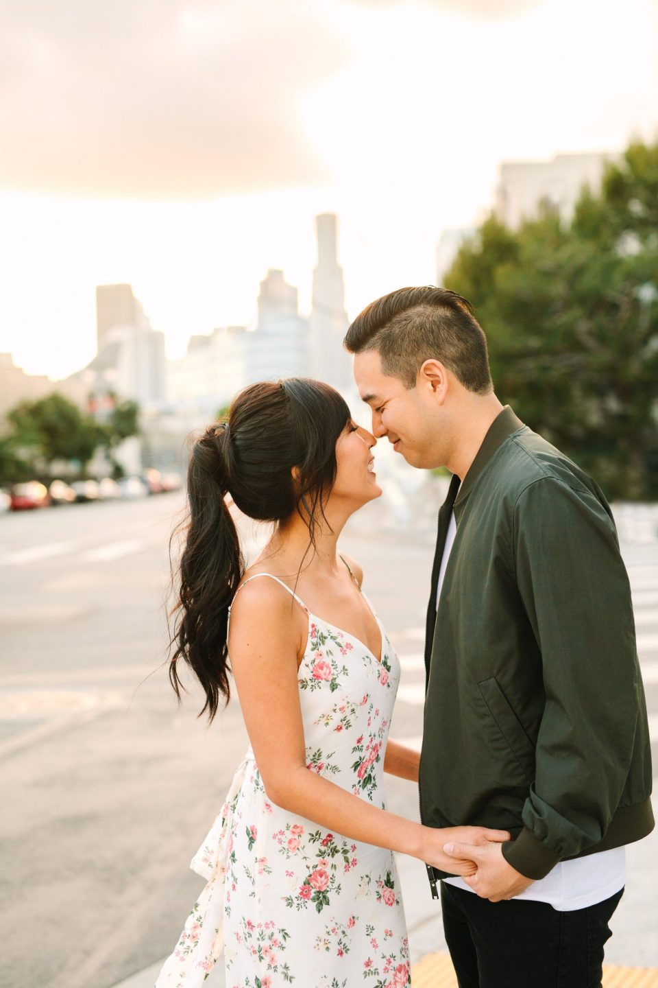 Couple snuggling with LA skyline behind them by Mary Costa Photography