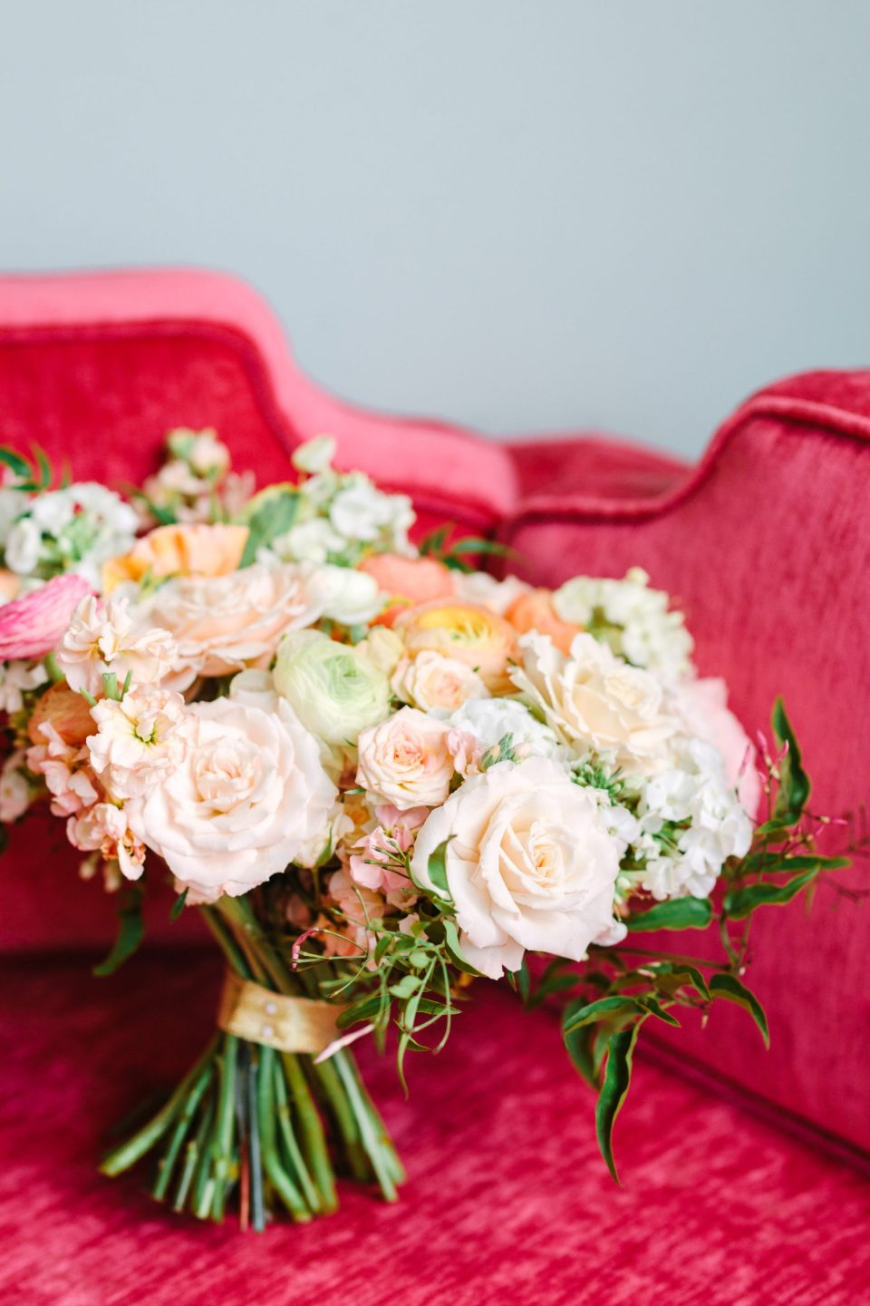 Bridal bouquet on pink couch by Mary Costa Photography