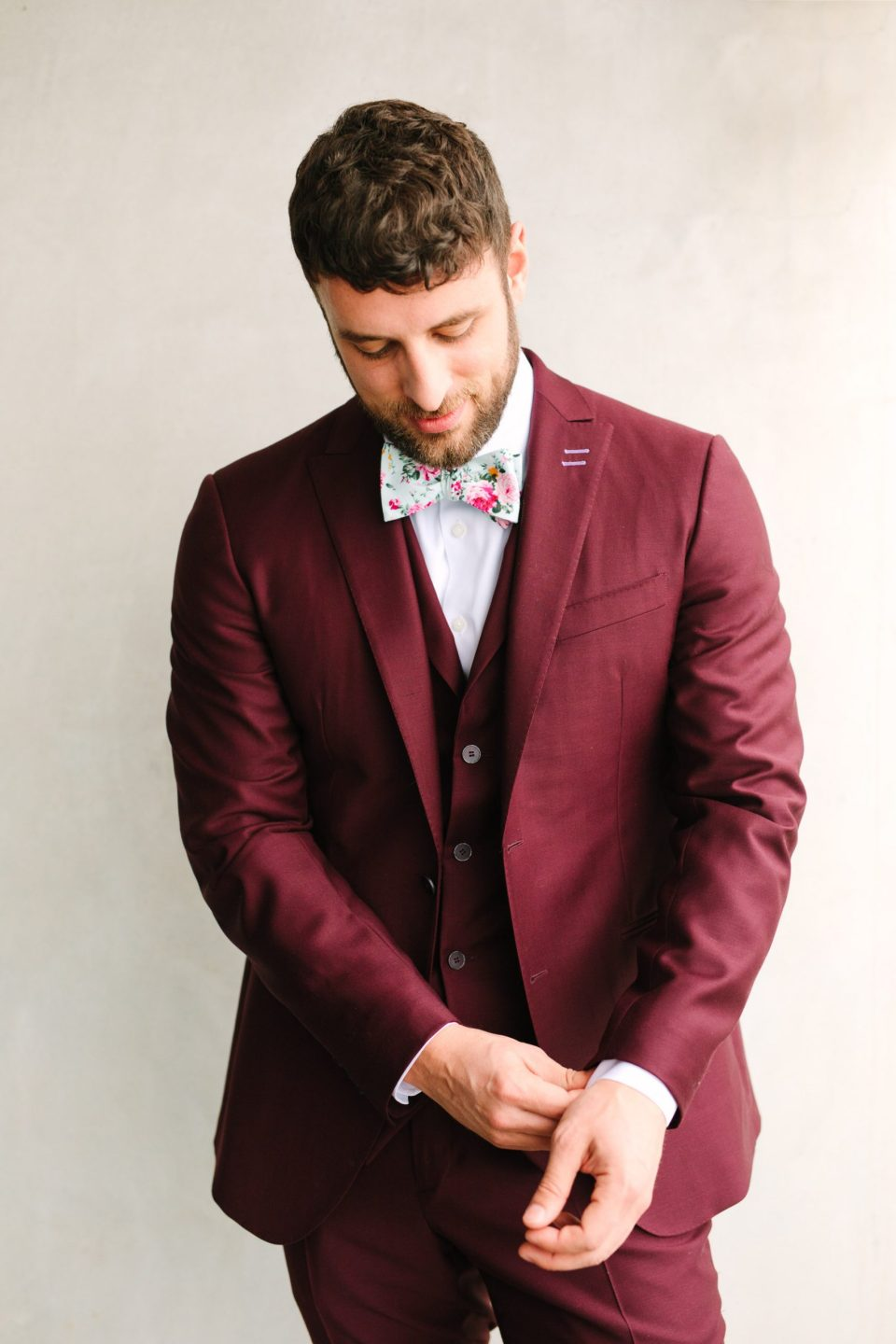 Groom getting ready in burgundy tux by Groom getting ready in emerald tux by Mary Costa Photography