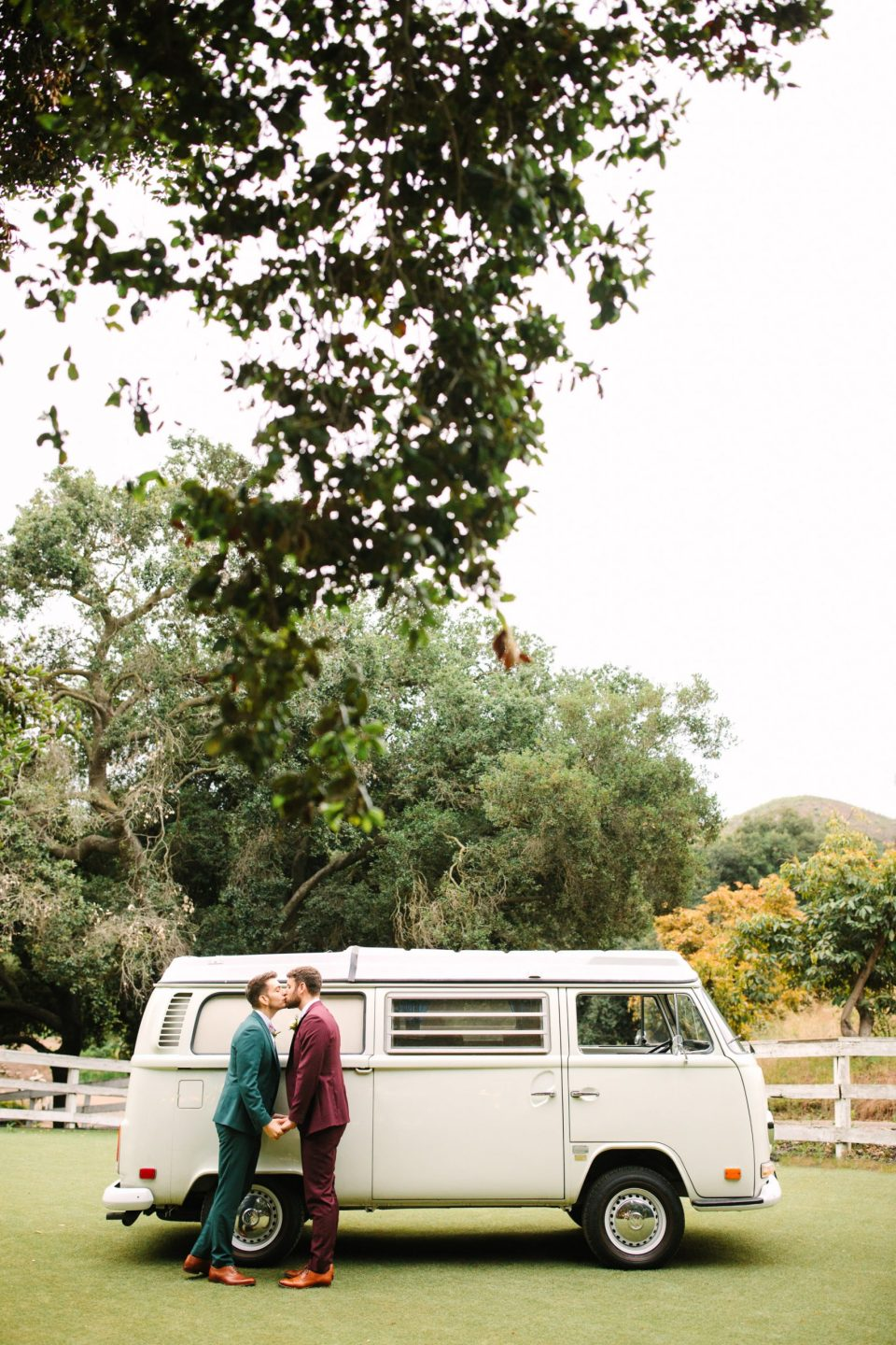 Two grooms kissing with VW van by Mary Costa Photography