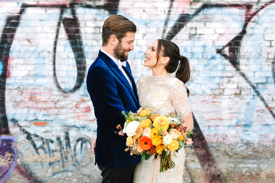 Bride and groom with graffiti backdrop www.marycostaweddings.com
