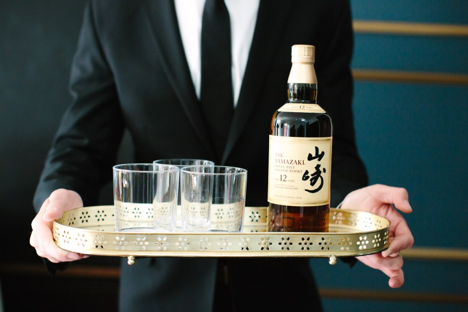 Groomsman holding Yamazaki 12 whiskey www.marycostaweddings.com
