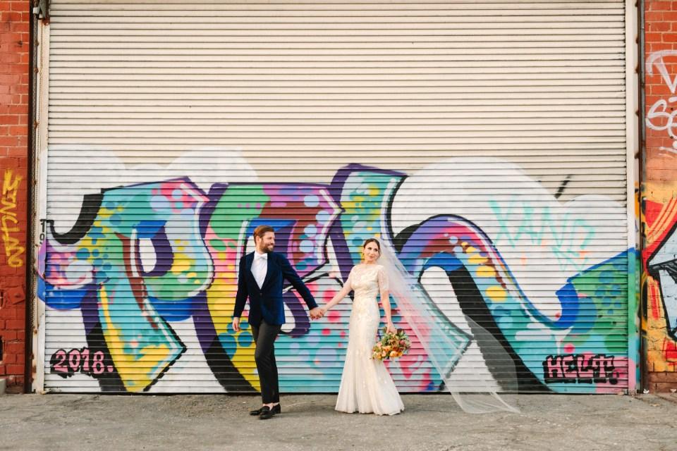 Bride and groom walking with graffiti www.marycostaweddings.com