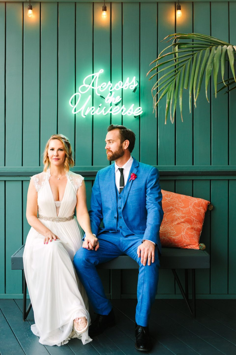 Bride and groom with Across the Universe neon sign at Ruby Street Los Angeles - www.marycostaweddings.com