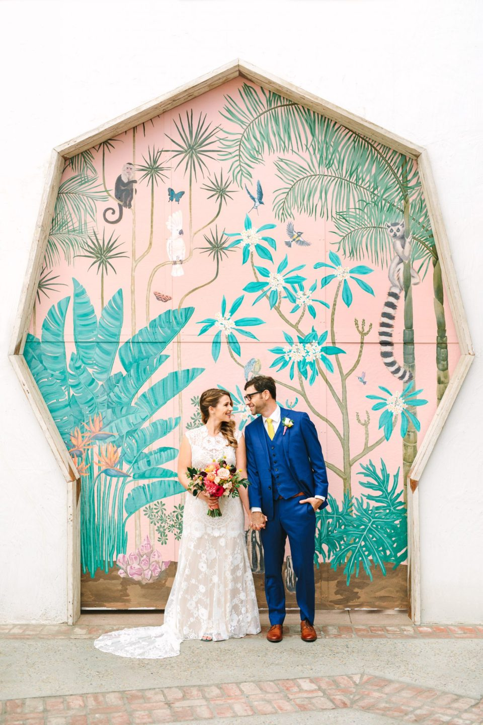 Bride and groom laughing in front of colorful door at Valentine DTLA - www.marycostaweddings.com
