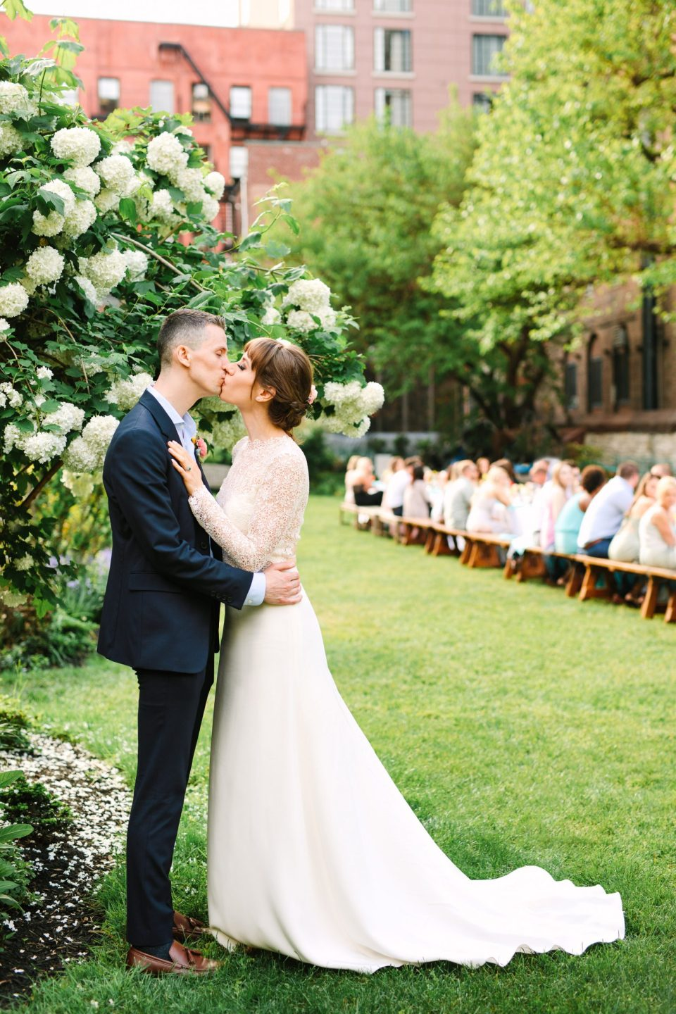 Emily and Luke kissing with guests in the background - www.marycostaweddings.com