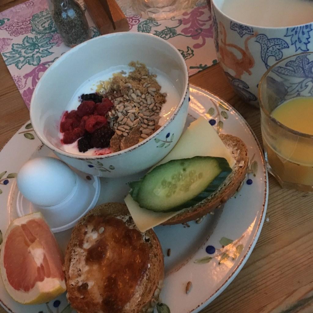frukosttallrik med ägg, smörgåsar, yoghurt med flingor och bär samt apelsinjuice och te